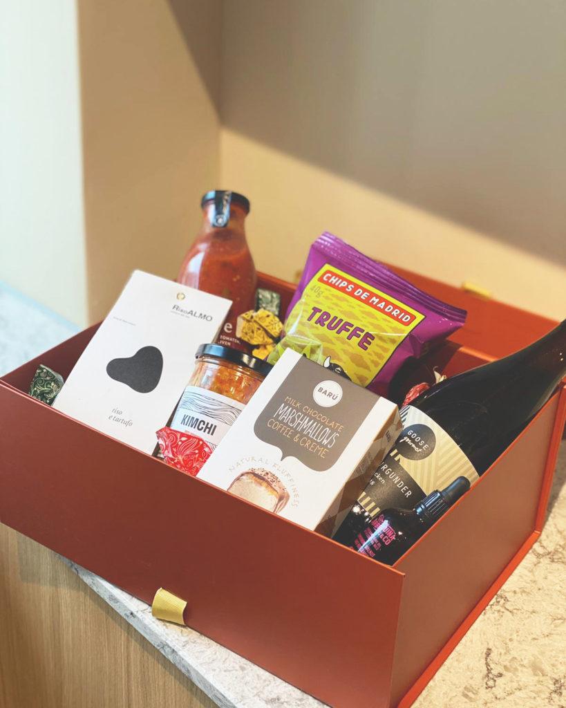 Präsentbox aus hochwertigen Produkten wie Gourmet Marshmallows, Trüffelchips, Trüffelrisotto und Wein. Präsentbox auf weißem Marmorboden.